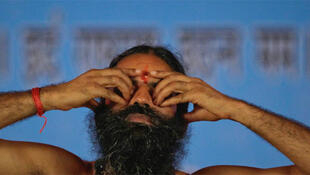 Swami Ramdev performs yoga at the Ramlila grounds on the first day of his fast