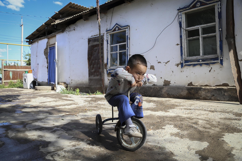 Alif Baqytali juega en un triciclo en su casa de Shonzhy, Kazajstán, el sábado 13 de junio de 2020. La madre de Baqytali, Gulnar Omirzakh, nacida en China y de etnia kazaja, dice que fue obligada a conseguir un dispositivo anticonceptivo intrauterino, y que las autoridades amenazaron con detenerla si no pagaba una gran multa por dar a luz a Alif, su tercer hijo. (Foto AP/Mukhit Toktassyn)