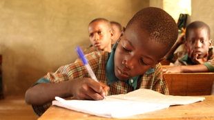 A boy takes notes during a sociology class at the Future Islamic Prowess Foundation. The school offers both Islamic and Western education.