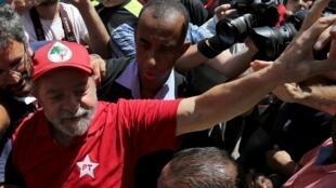 L'ancien président brésilien Lula soutenu par des supporters devant sa maison, le 5 mars 2016.