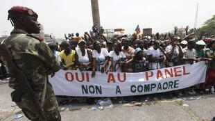 "A soldier standing in front of Gbagbo supporters holding a banner reading, ""Yes to the panel, no to Compaore"", Burkina Faso's president. Abidjan, 5 February"