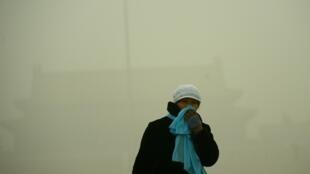 Uma mulher se protege com o cachecol enquanto anda pela Praça de Tiananmen por causa da forte poluição em Pequim, em 1° dezembro de 2015.