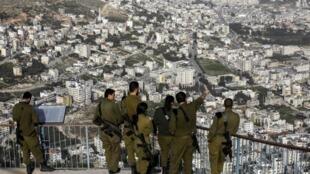 Des soldats israéliens contemplent la ville palestinienne de Nablus.