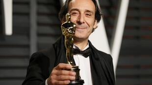 Composer Alexandre Desplat holds his award at the 2015 Oscars.