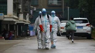 Des travailleurs du département local de prévention et de contrôle des maladies en tenue de protection désinfectent une zone résidentielle à la suite de l'apparition d'un nouveau coronavirus, à Ruichang, province du Jiangxi, Chine, 25 janvier 2020.
