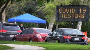 A police officer mans the entrance to a coronavirus (COVID-19) testing center in Hansen Dam Park in Pacoima, California