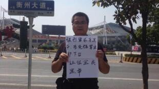 图为中国维权人士王美余公开举牌要求习李下台网络照片