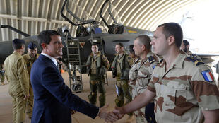 French Prime Minister Manuel Valls visits pilots from the French Air Forces close to Mirage 2000D (back) at the 101 Air-base in Niamey on 23 November 2014.