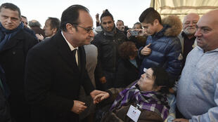 President François Hollande talks to Violette Gureme, a former inmate at Montreuil-Bellay