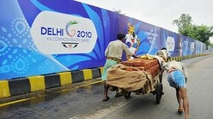 Labourers  in front of boards advertising the Commonwealth Games in New Delhi