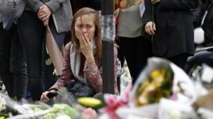 Mulher presta homenagem às vítimas dos atentados em Paris em frente ao restaurante Le Petit Cambodge.