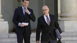 French Interior Minister Bernard Cazeneuve and Prime Minister Manuel Valls leave after the weekly cabinet meeting at the Elysee Palace in Paris, April 22, 2015.