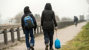 Migrants walk along a road leading to Calais in northern France