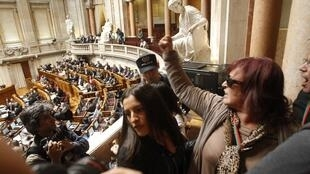 Policiais expulsam portugueses que protestam durante a apresentação do orçamento para 2014 no Parlamento, em Lisboa, nesta sexta-feira, 1° de novembro de 2013.
