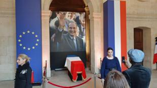 Le cercueil de Jacques Chirac, recouvert du drapeau tricolore, a été placé dans l'entrée de la cathédrale devant une immense photo le montrant souriant au milieu d'une foule.