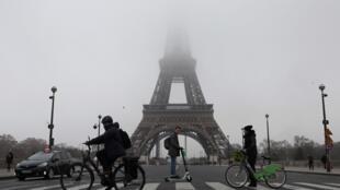 Les gens passent en vélo et en scooter électrique devant la tour Eiffel.