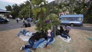 Migrants sit at the Franco-Italian border, 12 June 2015