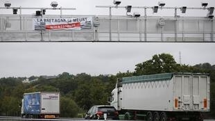 """Lorries pass under an ecotax control portal with a banner declaring """"Brittany is dying"""""""
