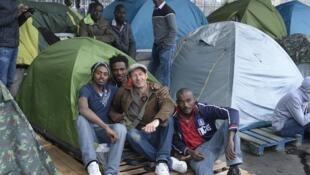 Le photographe Jean-Baptiste Pellerin avec des habitants du camp Coubri, situé sous le métro La Chapelle, à Paris, et démantelé le 1er juin 2015.