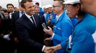 Emmanuel Macron cumprimenta empregados de um estaleiro naval em Saint-Nazaire, no oeste da França.