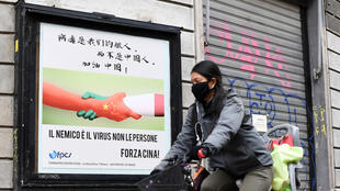 """""""The enemy is the virus, not the people,"""" reads the Italian in a poster in Milan. The Chinese reads: """"The virus is our enemy, not the Chinese."""""""