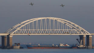 Chiến đấu cơ của Nga bay phía trên cây cầu nối Nga và Crimée, bên dưới là tầu chở hàng nằm chắn ngang sau khi ba tầu chiến Ukraina bị bắt ở eo biển Kerch Strait, ngày 25/11/2018.