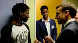 O presidente francês, Emmanuel Macron, conversa com um migrante sudanês no centro de acolhimento de Croisilles, no norte da França.
