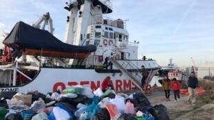 Des bénévoles aident au chargement de dons de couverture sur le bateau de l'ONG OpenArms.