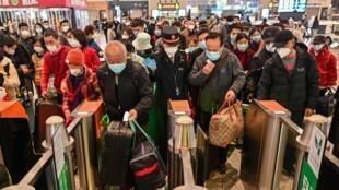 Decenas de pasajeros con mascarillas se disponen a pasar los tornos de una estación ferroviaria para acceder a un tren que tiene en Wuhan una de sus paradas, el 28 de marzo de 2020 en la ciudad china de Shanghái
