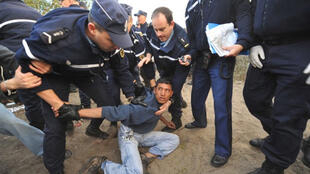 French police arresting an Afghan asylum seeker in Calais in 2009