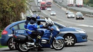 Les gendarmes se tiennent près de l'autoroute A1 alors qu'ils contrôlent la vitesse des voitures, près de Fresnes-les-Montauban, dans le nord de la France.