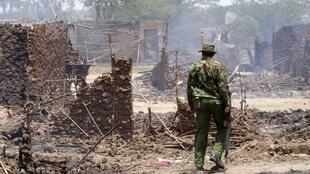 A policeman walks through the remains of a burnt village after an attack in the Tana River Delta, 11 September, 2012
