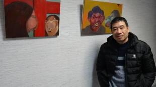 Họa sĩ Lê Anh Hoài với các tác phẩm của anh trưng bày tại Trung tâm Văn hóa Việt Nam, Paris.