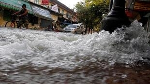 People walk in a flooded street in central Bangkok. Receding floodwaters north of Bangkok have reduced the threat