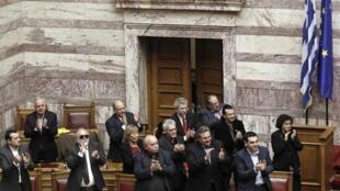 O primeiro-ministro grego, Alexis Tsipras, e membros do governo aplaudem o voto de confiança do Parlamento em Atenas.