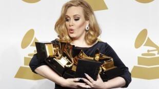 A cantora Adele segura seus seis prêmios Grammy, na Califórnia, neste domingo.
