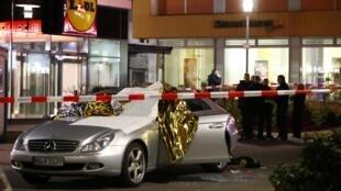 Un corps est allongé derrière cette voiture endommagée par l'une des deux fusillades survenues à Hanau, dans la soirée du 19 février 2020.