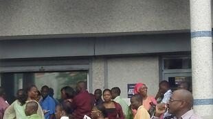 Customers line up to withdraw money outside a bank in Abidjan
