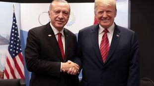 A handout picture released by the Turkish Presidential Palace Press Office shows Turkey's President Recep Tayyip Erdogan (L) posing with US President Donald Trump during the G20 summit in Buenos Aires, Argentina, on December 1, 2018.
