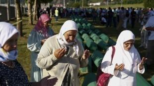 Les femmes prient près des cercueils de leurs proches, victimes nouvellement identifiées du massacre de Srebrenica de 1995, qui sont alignés pour un enterrement commun à Potocari près de Srebrenica, en Bosnie-Herzégovine, le 11 juillet 2017.