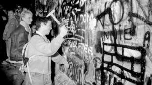 1989年11月9日,在西德宣布开放边界后,一位男子用铁锤敲击靠近勃登堡门附近的柏林墙。