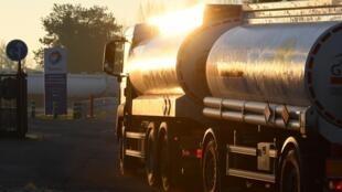 Un camion-citerne entre dans une station-service près d'un dépôt de carburant.