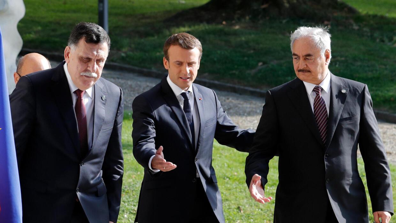 Fayez al-Sarraj (g) et Khalifa Haftar (d) entourent le président français Emmanuel Macron, le 25 juillet 2017 à la Celle-Saint-Cloud. (Photo d'illustration)