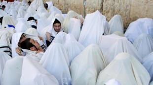 Envolvidos nos tradicionais xales brancos de orações, judeus se reuniram diante do Muro de Lamentações