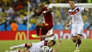 O ganense Andre Ayew (centro) pula o alemão Toni Kroos sob o olhar de Bastian Schweinsteiger (à direita).