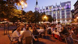 Des touristes attablés aux terrasses de cafés situés sur la Calle de Huertas, à Madrid.