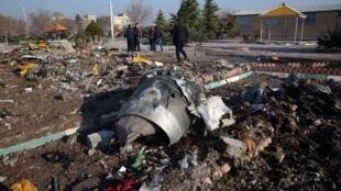Des secouristes marchent au milieu des débris du vol PS752 de l'Ukrainian International Airlines le 8 janvier 2020.