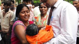 Родственники оплакивают детей, погибших в больнице в Лакхнау, 12 августа 2017 года.