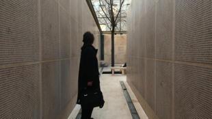 Une personne contemple le mur des Noms qui porte, gravés dans la pierre, les noms, prénoms et dates de naissance des 76000 juifs déportés de France entre 1942 et 1944, sur le parvis du Mémorial de la Shoah dans le Marais, à Paris.