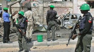 African Union Mission in Somalia (AMISOM) troops patrol following a blast close to the heavily fortified gates of the airport in Mogadishu on December 2014.